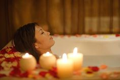 Woman taking bath, with candles and flower petals.